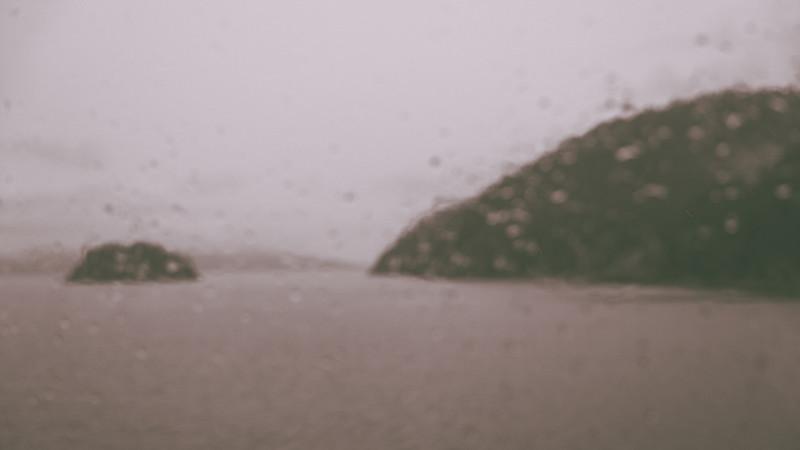 A blurry and foggy outside seen through a rain-dabbled ferry window.