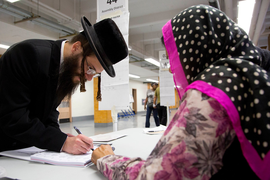 . Yitzchok Hershowitz, left, signs in to vote with poll inspector Shahnaz Kadir, originally from Bangladesh, at a polling site, Tuesday, Nov. 4, 2014 in the Brooklyn borough of New York. (AP Photo/Mark Lennihan)