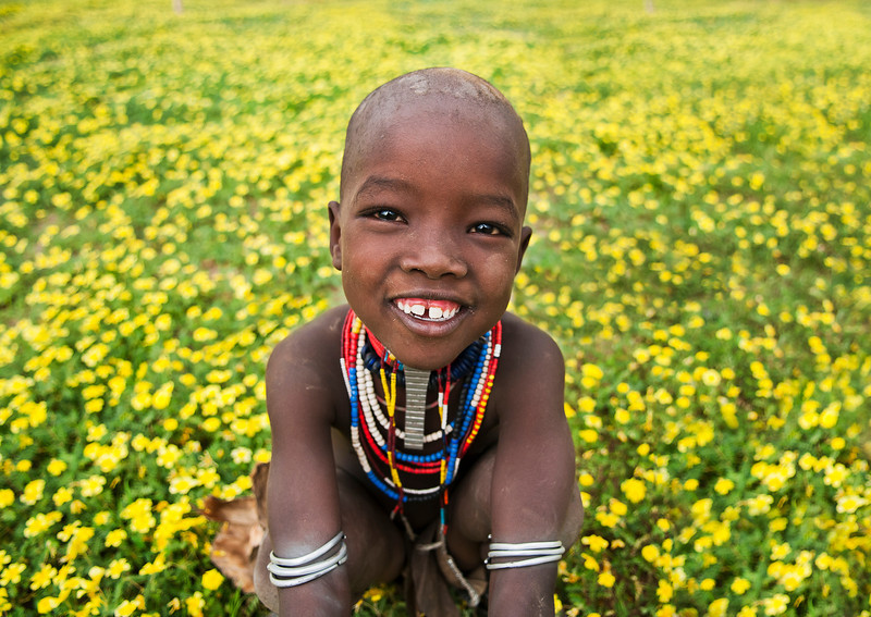 Little girl from the Arbore tribe in a field of flowers. 
