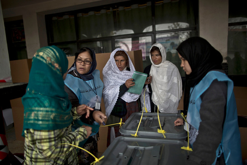 . An Afghan election worker, second left, explains the process of elections to voters at a polling station in Kabul, Afghanistan, Saturday, April 5, 2014. Afghan voters lined up for blocks at polling stations nationwide on Saturday, defying a threat of violence by the Taliban to cast ballots in what promises to be the nation\'s first democratic transfer of power. Partial results are expected as soon as Sunday. (AP Photo/Muhammed Muheisen)