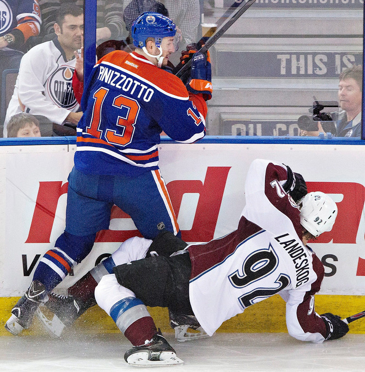 . Colorado Avalanche\'s Gabriel Landeskog (92) is checked by Edmonton Oilers\' Steven Pinizzotto (13) during second period NHL hockey action in Edmonton,  Alberta, on Tuesday April 8, 2014. (AP Photo/The Canadian Press, Jason Franson)