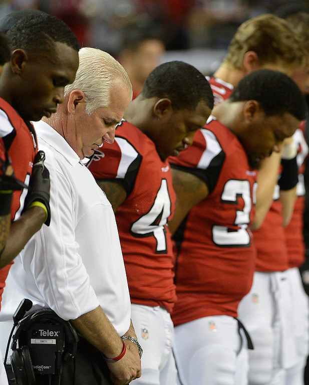 . Atlanta Falcons head coach Mike Smith, second from left, and players close their eyes during during a moment of silence for the victims of the Sandy Hook Elementary School shootings before an NFL football game against the New York Giants, Sunday, Dec. 16, 2012, in Atlanta. A gunman walked into the school in Newtown, Conn., Friday and opened fire, killing 26 people, including 20 children. (AP Photo/Rich Addicks)
