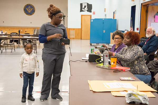 11/05/19 Wesley Bunnell | StaffrrVira Riley, 3rd L, and Francina Sloan, 4th L, assist Trena Edney at the check in table at the VFW 511 voting location early Tuesday afternoon. Edney is accompanied by her 4 year old daughter Sa'har Register.