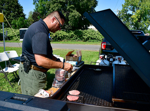 9/29/2018 Mike Orazzi | Staff New Britain Police Traffic division's Peter Scirpo cooks hamburgers during the annual charity softball game between the New Britain fire and police departments at Chesley Park. This year, the fire department decided to raise money for New Britain-based Connecticut Breast Health Initiative, an organization that raises money and distributes it to breast cancer-related research and education in the state. CT BHI was picked this year in honor of New Britain Police Department Lt. Julia Gallup, who was diagnosed with breast cancer earlier this year and has been fighting the disease since.