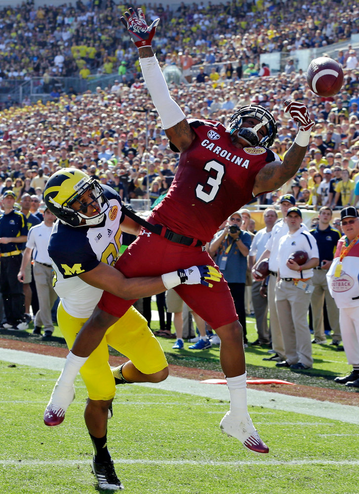 Description of . South Carolina cornerback Akeem Auguste (3) breaks up a pass intended for Michigan wide receiver Joe Reynolds (85) during the first quarter of the Outback Bowl NCAA college football game, Tuesday, Jan. 1, 2013, in Tampa, Fla. (AP Photo/Chris O'Meara)