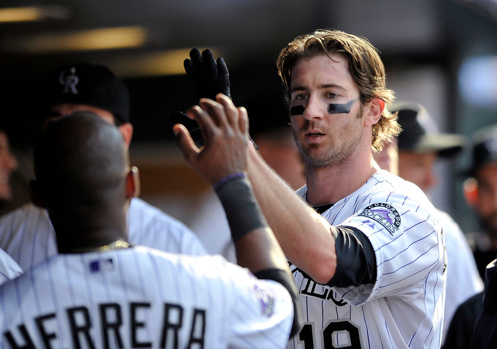 . Colorado Rockies\' Charlie Blackmon is congratulated by teammates in the dugout after scoring on a Corey Dickerson RBI triple off St. Louis Cardinals relief pitcher Trevor Rosenthal during the eighth inning of a baseball game Thursday, Sept. 19, 2013, in Denver. (AP Photo/Jack Dempsey)