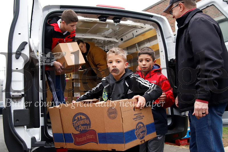 Evan Orday, 8, unloads a box of food for donation to the Lighthouse Foundation Tuesday with his brothers Grant, 11, (right) and Seth, 13.