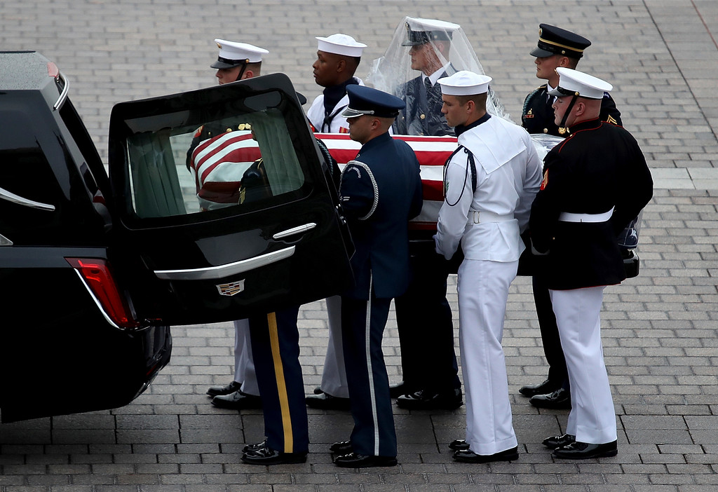 . A military honor guard team places the casket of Sen. John McCain, R-Ariz., into a waiting hearse at the U.S. Capitol, Saturday, Sept. 1, 2018 in Washington.  (Win McNamee/Pool photo via AP)