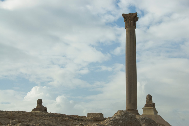 Pompey's Pillar in between Egyptian statues - Alexandria, Egypt