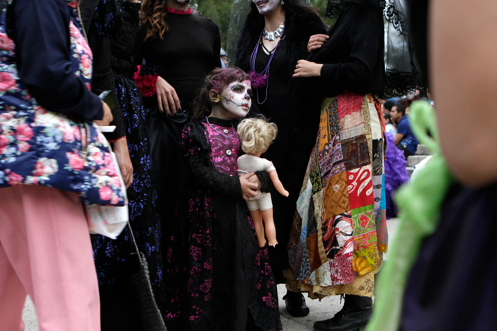 ". Nina, 5, dressed as a ""Catrina,\"" or skeleton lady waits with her mother for the start Gran Procession of the Catrinas, to mark the upcoming Day of the Dead holiday, in Mexico City, Sunday, Oct. 23 2016. The gran procession is one of many that will take place in Mexico City as part of the celebrations, culminating with visits to the graves of departed loved ones on Nov. 1 and 2. The figure of a skeleton wearing broad-brimmed hat was first done as a satirical engraving by artist Jose Guadalupe Posada sometime between 1910 and his death in 1913, to poke fun at women who pretended to be European by dressing elegantly and as a critique of social stratification. (AP Photo/Anita Baca)"
