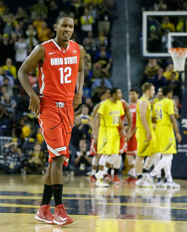 . Ohio State forward Sam Thompson walks back to the bench as the Michigan team celebrates during the second half of an NCAA college basketball game, Sunday, Feb. 22, 2015 in Ann Arbor, Mich. Michigan defeated Ohio State 64-57. (AP Photo/Carlos Osorio)