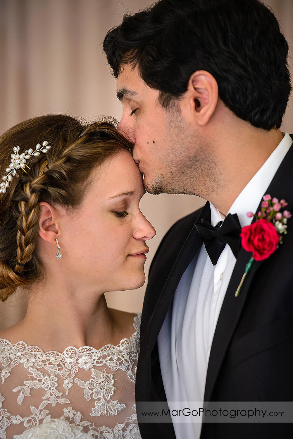 groom kissing bride's forehead at wedding reception at Fremont Century House & Gardens