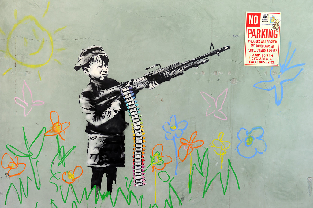 ". A graffiti attributed to secretive British artist Banksy depicting a child wielding a machine gun, in black and white surrounded by colored flowers, is spotted in Westwood, California on February 17, 2011. Another graffiti was ripped down Wednesday, February 16th in Hollywood, amid sightings of other pieces in a reported pre-Oscars publicity stunt. Banksy is nominated for best documentary for ""Exit Through the Gift Shop\"" at the Oscars, due to be announced on February 27th at the climax of Tinseltown\'s annual awards season.  (GABRIEL BOUYS/AFP/Getty Images)"
