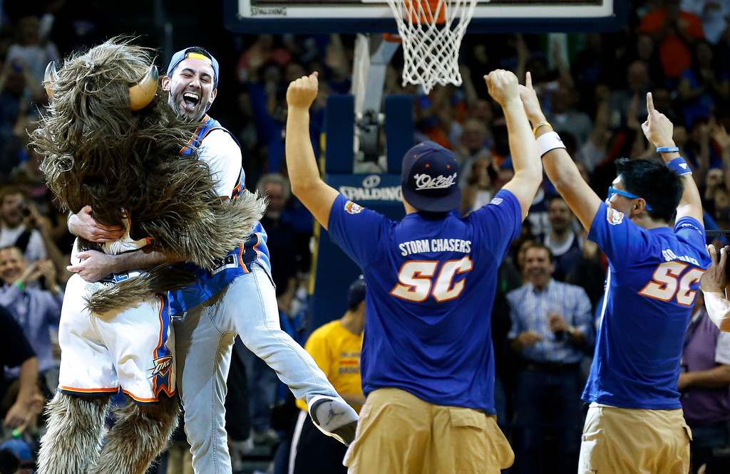 . Cameron Rodriguez, second from left, celebrates with Thunder mascot Rumble, left, after hitting a half court shot to win $20,000 during a time out of an NBA basketball game between the Oklahoma City Thunder and the Denver Nuggets in Oklahoma City, Monday, Nov. 18, 2013. (AP Photo/Sue Ogrocki)