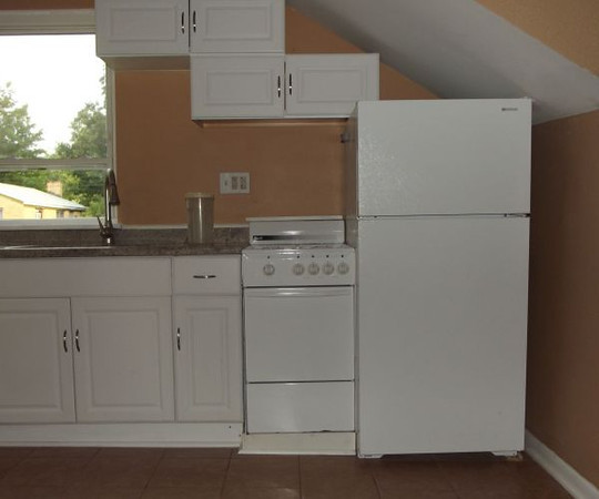 The kitchenette in the third-floor studio efficiency has compact cupboards, gas oven, refrigerator, stainless steel double sink and granite counter top.