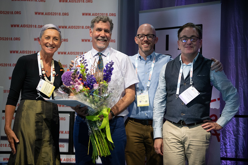 22nd International AIDS Conference (AIDS 2018) Amsterdam, Netherlands.   Copyright: Steve Forrest/Workers' Photos/ IAS  Photo shows: President of the IAS, Linda-Gail Bekker presenting flowers to Immediate Past President, Chris Beyrer, during the IAS Members' Meeting. From Left to Right: Linda-Gail Becker, Chris Beyrer, Owen Ryan, Kevin Osborne.