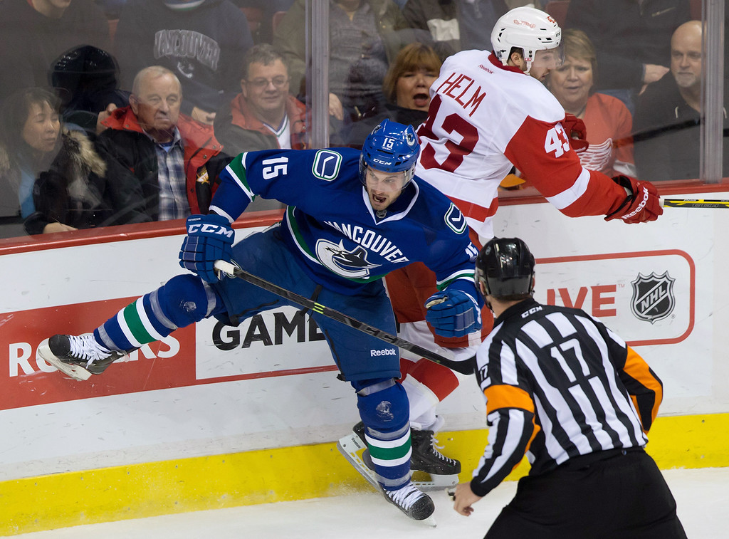 . Vancouver Canucks\' Brad Richardson, left, and Detroit Red Wings\' Darren Helm collide during the third period of an NHL hockey game in Vancouver, British Columbia, Saturday, ja. 3, 2015. (AP Photo/The Canadian Press, Darryl Dyck)