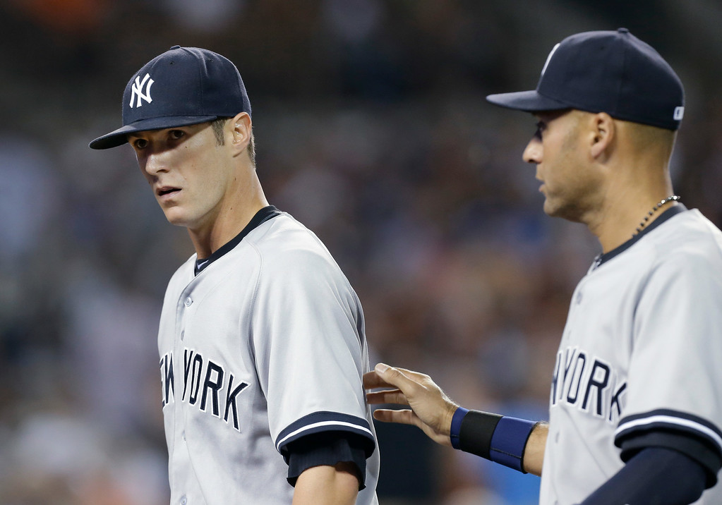 . New York Yankees pitcher Shane Greene, left, is patted on the back by teammate Derek Jeter after the fourth inning of a baseball game against the Detroit Tigers in Detroit, Wednesday, Aug. 27, 2014. (AP Photo/Paul Sancya)