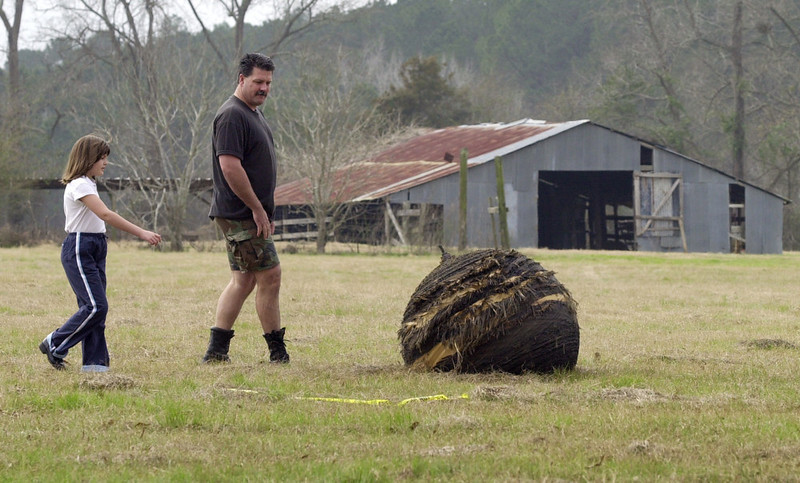 . Tommy Peltier of Houston and his daughter Alexis, 8, approach a large piece of debris from space shuttle Columbia that fell close to their family\'s home near San Augustine, Texas, Sunday, Feb. 2, 2003. After the shuttle broke up Saturday over eastern Texas, fragments of the shuttle were sent showering to the ground. (AP Photo/Eric Gay)