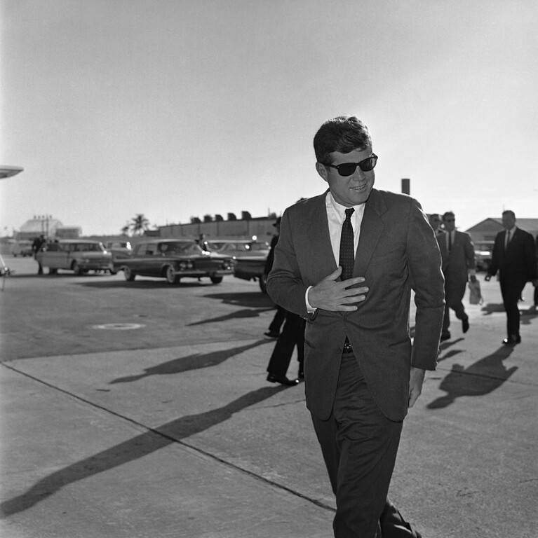 . 1961: John F. Kennedy. President John F. Kennedy heads for Washington after an overnight stopover on Dec. 19, 1961 in West Palm Beach, Florida where he rested after his latin tour due to a heavy cold. Wearing sun glasses he manages a smile. (AP Photo)