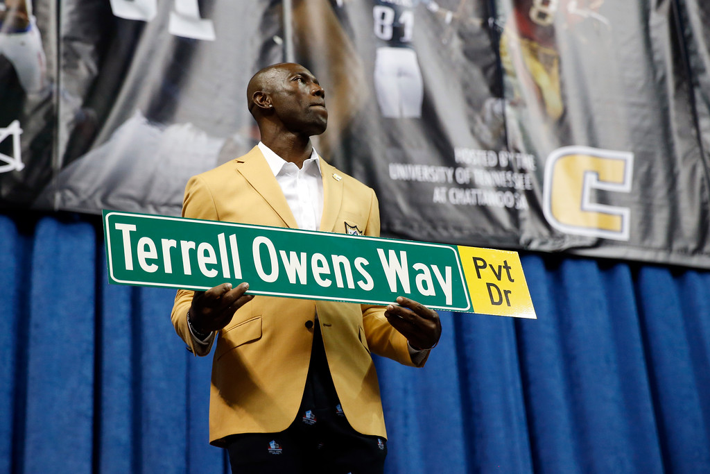 . Former wide receiver Terrell Owens holds a street sign after a road was named after him following his NFL Pro Football Hall of Fame speech on Saturday, Aug. 4, 2018, in Chattanooga, Tenn. Instead of speaking at the Hall of Fame festivities in Canton, Ohio, Owens celebrated his induction at the University of Tennessee at Chattanooga, where he played football and basketball and ran track. (AP Photo/Mark Humphrey)