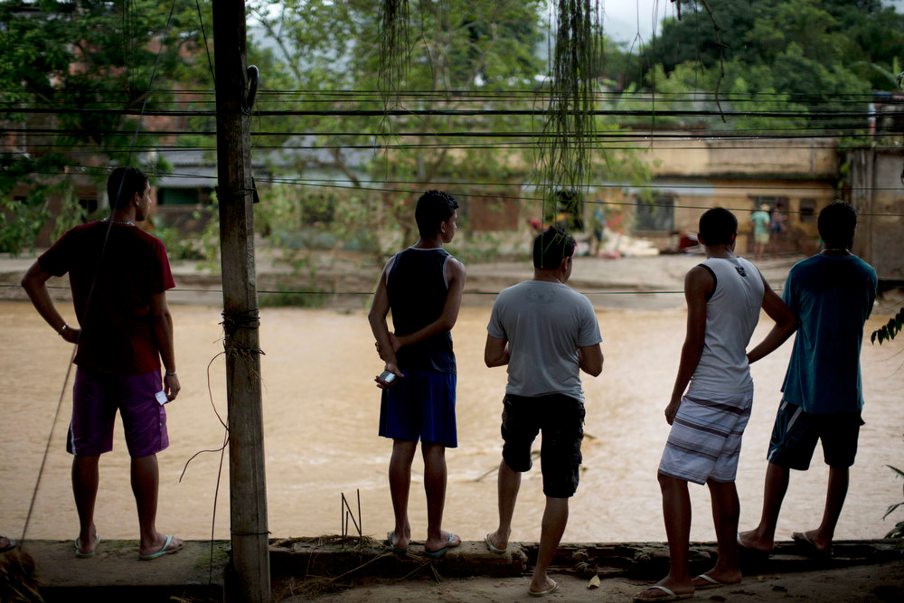 Description of . Residents watch the rising Capivari River in the Xerem neighborhood, about 31 miles north of Rio de Janeiro, Brazil, where heavy rains caused flooding, Thursday, Jan. 3, 2013. Nearly 8.5 inches of rain fell in just 24 hours in the mountainous region north of Rio. Hard rains in Brazil are creating a state of alert in Rio de Janeiro and in nearby spots where flood-triggered mudslides have killed hundreds in recent years. (AP Photo/Felipe Dana)