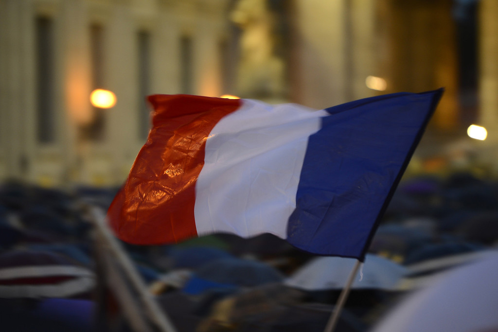 . A faithful waves a French flag as the crowd waits for the smoke announcing the result on the second day of the papal election conclave on March 13, 2013 at the Vatican.   AFP PHOTO / ANDREAS SOLARO/AFP/Getty Images