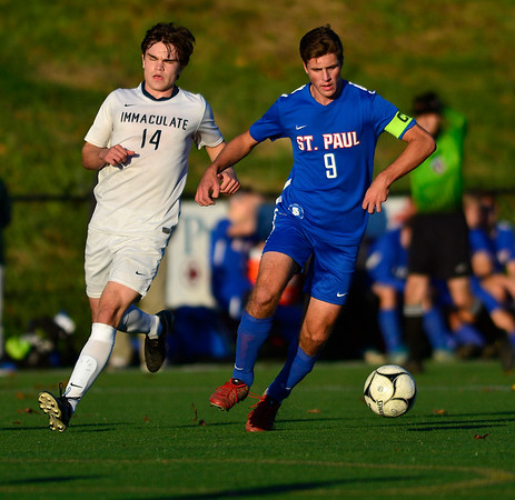 11/8/2018 Mike Orazzi | Staff St. Paul Catholic High School's Stefan Zwolinski (9) and Immaculate High School's Quinn Guth (14) during the Class S Second Round Boys Soccer Tournament held at the Farmington Sports Arena Thursday.