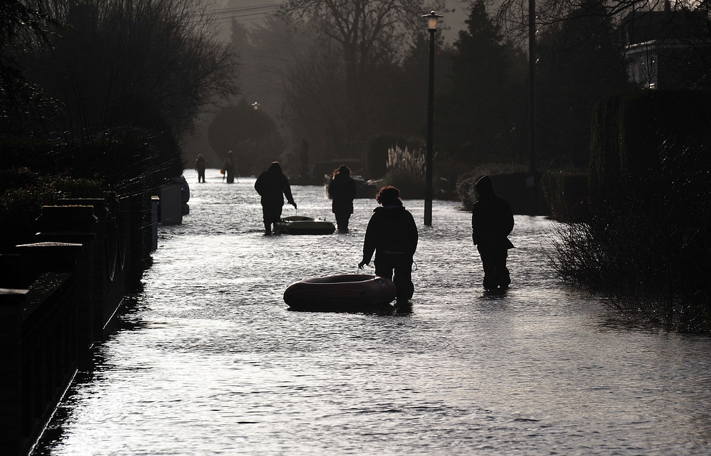 . People walk along a flooded road in Wraysbury, west of London on February 12, 2014.  Flooded communities in Britain faced a fresh battering from storms and high winds, with hundreds more homes threatened by the advancing waters. Gusts approaching 100 miles (160 kilometres) per hour tore at parts of England and Wales, and the River Thames was predicted to rise to its highest level in more than 60 years in places, threatening towns and villages to the west of London.  AFP PHOTO / CARL COURTCARL COURT/AFP/Getty Images