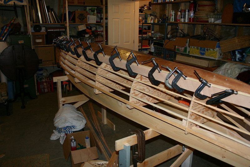 """The basic process for building the canoe involves attaching plywood strips, called """"strakes"""" to each other with epoxy glue, using the form to hold them in place until they dry. The strakes overlap, hence the name for this style of canoe -- """"lapstrake."""""""