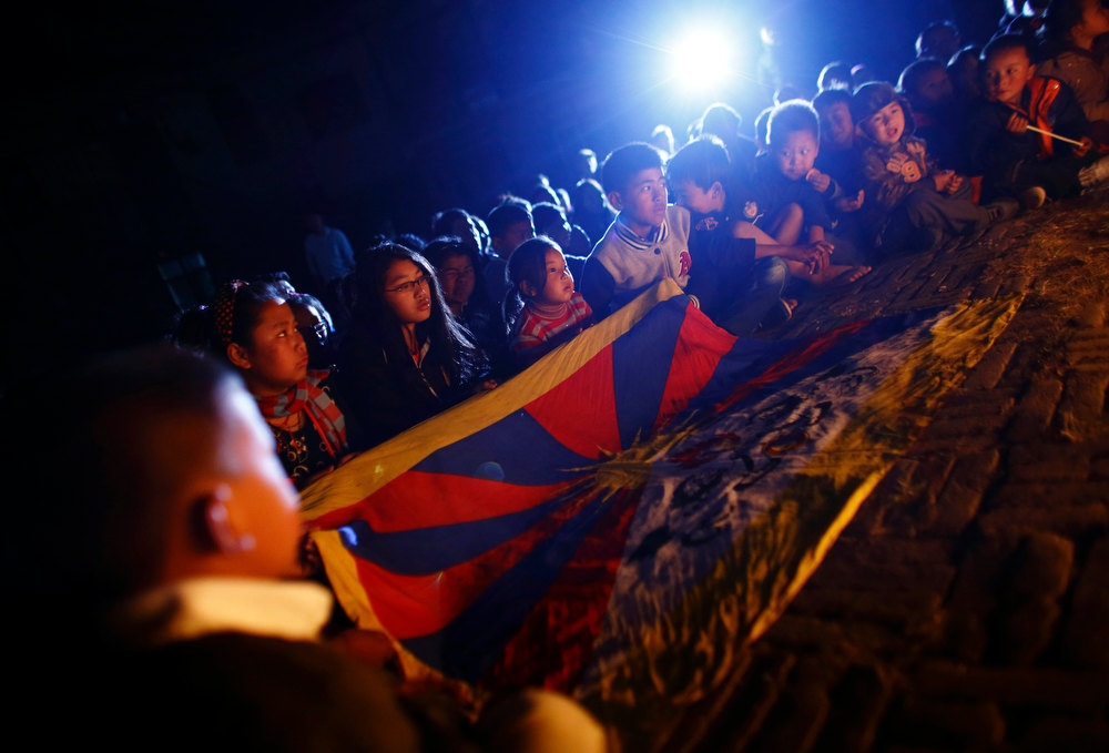Description of . Tibetan children sit near a Tibetan flag during a candlelight vigil to show solidarity to Tibetans who have self-immolated, and to mark the 100th anniversary of the 1913 Tibetan Proclamation of Independence, at the Tibetan Refugee Camp in Lalitpur February 13, 2013. A Tibetan monk self-immolated on Wednesday at the premises of the Boudhanath Stupa in Kathmandu. REUTERS/Navesh Chitrakar