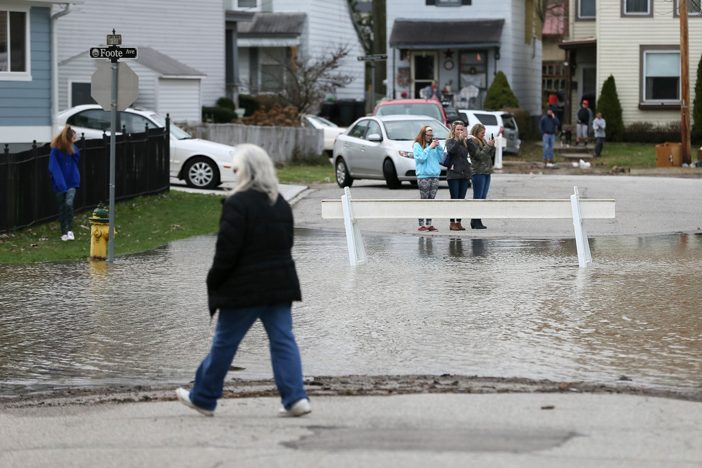 . Residents of Bellevue, Ky., take pictures of flood waters at the intersection of Foote Avenue and Frank Benke Way, Sunday, Feb. 25, 2018. The weather service said moderate flooding was expected along the Ohio River in Kentucky and Ohio, including in Cincinnati, where the river was 8 feet above flood stage Sunday. (Kareem Elgazzar/The Cincinnati Enquirer via AP)