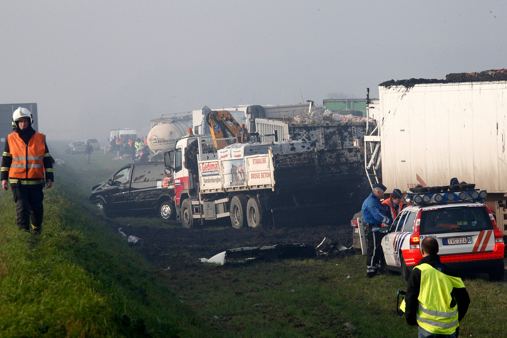 . Belgian police officers and firefighters gather at the scene of a pileup involving dozens of cars and trucks near Zonnebeke, Belgium, Tuesday, Dec. 3, 2013.  (AP Photo / Michel Spingler)