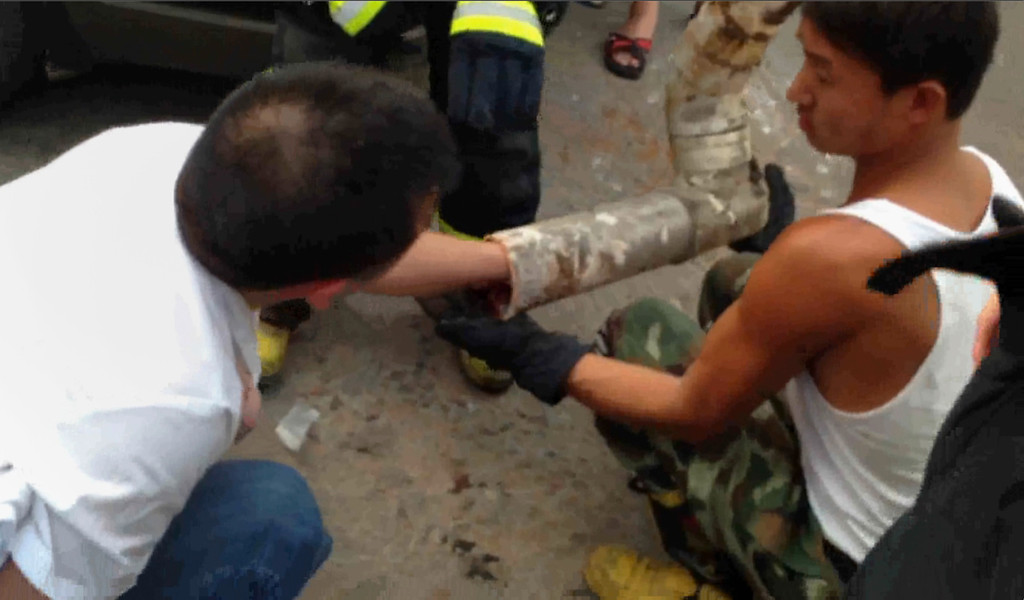 . This frame grab taken from AFPTV footage received on May 28, 2013 shows a rescue worker reaching into a pipe after a newborn baby boy got stuck inside in the city of Jinhua, in the eastern province of Zhejiang.      AFP PHOTO / AFPTVAFPTV/AFP/Getty Images
