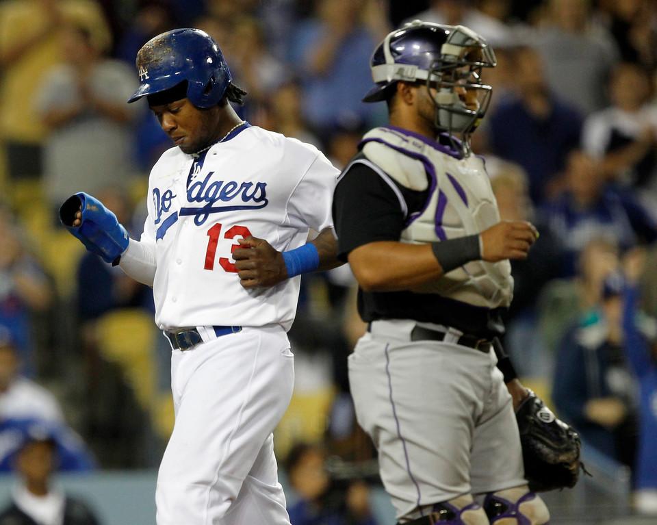 . Los Angeles Dodgersí Hanley Ramirez, left,  scores behind Colorado Rockies catcher Wilin Rosario, right, on a double by Dodgers\' Matt Kemp in the sixth inning of a baseball game on Monday, June 16, 2014, in Los Angeles.   (AP Photo/Alex Gallardo)