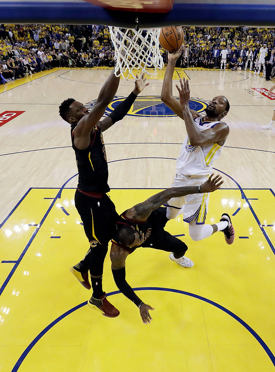 . Golden State Warriors\' Kevin Durant, right, draws a charging foul from Cleveland Cavaliers\' LeBron James, bottom center, during the second half of Game 1 of basketball\'s NBA Finals Thursday, May 31, 2018, in Oakland, Calif. (AP Photo/Marcio Jose Sanchez)