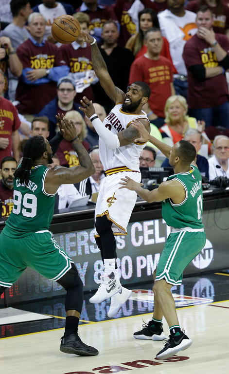 . Cleveland Cavaliers\' Kyrie Irving (2) passes against Boston Celtics\' Jae Crowder (99) and Avery Bradley (0) during the second half of Game 4 of the NBA basketball Eastern Conference finals, Tuesday, May 23, 2017, in Cleveland. The Cavaliers won 112-99. (AP Photo/Tony Dejak)