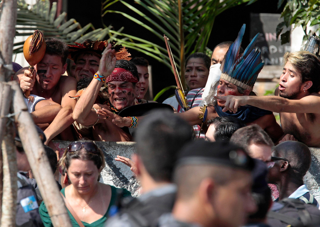 . Native Indians and their supporters shout during a protest at the Brazilian Indian Museum in Rio de Janeiro March 22, 2013. Brazilian military police took position early morning outside the Indian museum, where a native Indian community of around 30 individuals who have been living in the abandoned Indian Museum since 2006. Indians were summoned to leave the museum in 72 hours by court officials since last week, local media reported. The group is fighting against the destruction of the museum, which is next to the Maracana Stadium.  REUTERS/Sergio Moraes