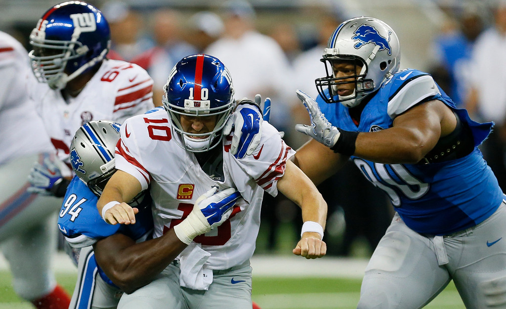 . New York Giants quarterback Eli Manning (10) is knocked down by Detroit Lions defensive end Ezekiel Ansah, left, and defensive tackle Ndamukong Suh (90) during the second quarter of an NFL football game in Detroit, Monday, Sept. 8, 2014. (AP Photo/Paul Sancya)