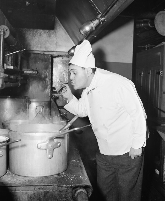 . Comedian-actor Zero Mostel acts as chef and tastes soup over a stove in the kitchen at La Martinique Club where he is appearing on stage in New York City, Jan. 24, 1944.  (AP Photo/Charles Kenneth Lucas)