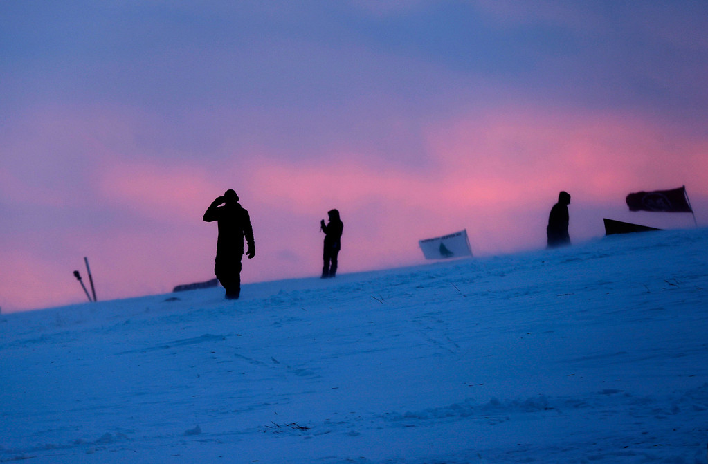 . People walk along a snowy hillside at the Oceti Sakowin camp where people have gathered to protest the Dakota Access oil pipeline in Cannon Ball, N.D., Monday, Dec. 5, 2016. Many Dakota Access oil pipeline opponents who\'ve gathered for months in the camp in southern North Dakota are committed to staying despite wintry weather and demands that they leave. (AP Photo/David Goldman)