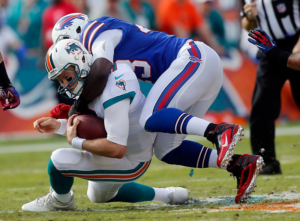 . Miami Dolphins quarterback Ryan Tannehill, bottom, is tackled by Buffalo Bills linebacker Bryan Scott (43) during the first half of an NFL football game on Sunday, Dec. 23, 2012, in Miami. (AP Photo/John Bazemore)