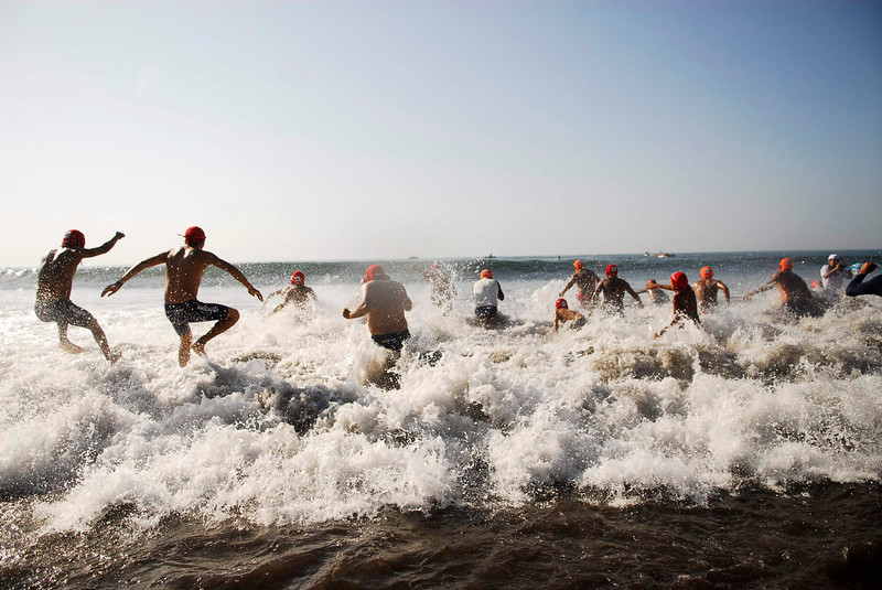 . Participants of the annual Paso del Hombre endurance challenge jump into the sea at La Libertad port in El Salvador February 24, 2013. About 370 male and female lifeguard volunteers swam for four to five hours continuously during the 49th edition of the event organized by the Salvadorian Red Cross in collaboration with the Navy, Coast Guard, Air Force and Civil National Police, local media reported. Picture taken February 24, 2013. REUTERS/Ulises Rodriguez