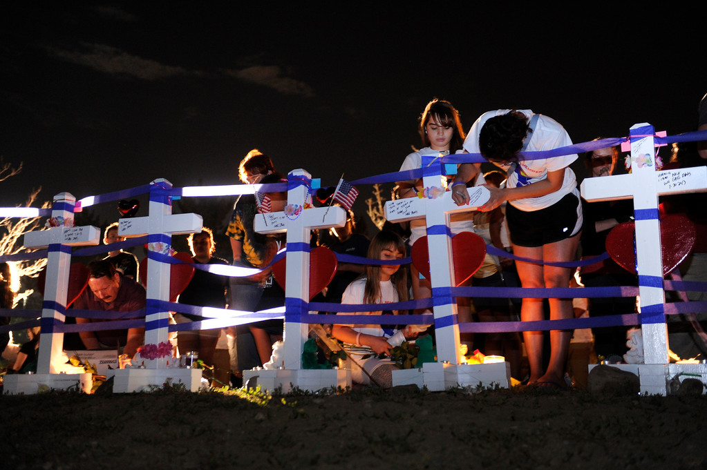 . AURORA, CO. - JULY 20: Hundreds of mourners marked the one year anniversary of the Aurora theater shootings Saturday morning, July 20, 2013.  Carpenter Greg Zanis put up 12 white, wooden crosses in an empty field across the street from the movie complex where a dozen persons lost their lives and scores more were injured. Zanis wants these crosses to go to the families after this weekend. Photo By Karl Gehring/The Denver Post