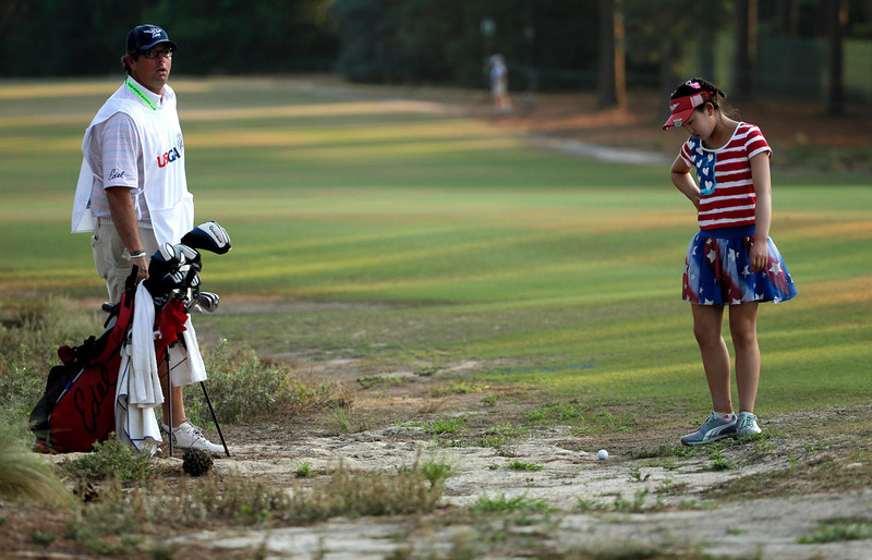 . Lucy Li checks out her lie in the waste area on the 11th fairway during the first round of the U.S. Women\'s Open golf tournament in Pinehurst, N.C., Thursday, June 19, 2014. Looking on is her caddie Bryan Bush. (AP Photo/Chuck Burton)