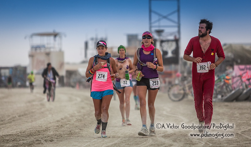 The women are competitively dressed while the guy decides to run in his sleepers while staying hydrated with a beer. Again, welcome to Burning Man.