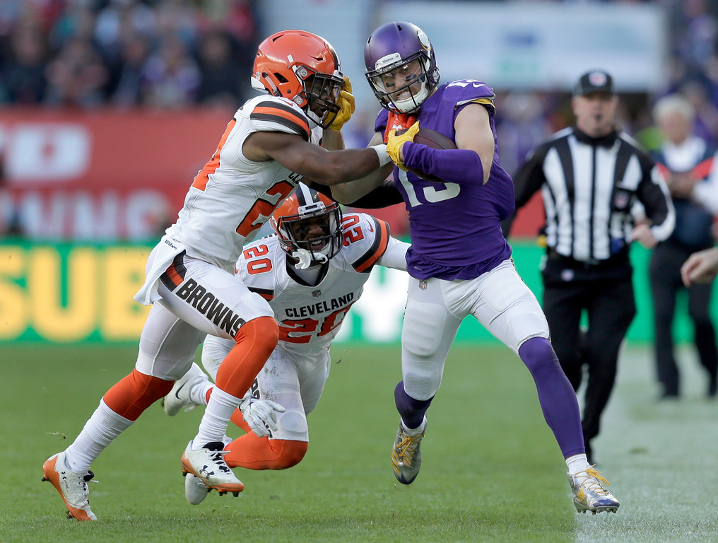 . Minnesota Vikings wide receiver Adam Thielen, right, is pushed out of bounds by Cleveland Browns\' Ibraheim Campbell, left, as Browns\' Briean Boddy-Calhoun, center, watches during the first half of an NFL football game at Twickenham Stadium in London, Sunday Oct. 29, 2017. (AP Photo/Tim Ireland)