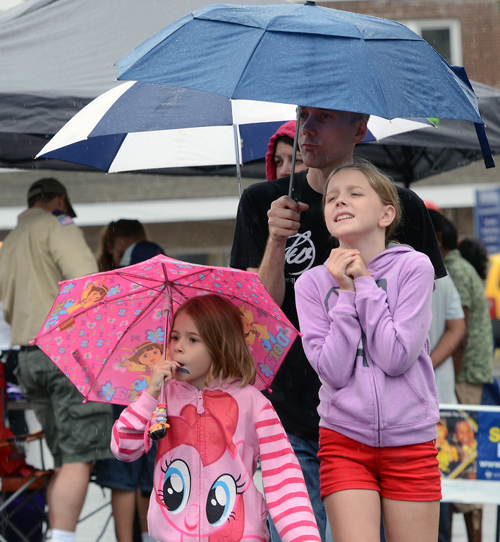 . The Braster family hudle under umbrellas as rain falls during the Lansdale Founders Day  celebration on Saturday August 23,2014. Photo by Mark C Psoras/The Reporter