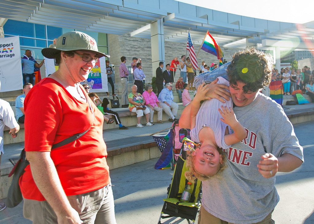 . Sarah Lester, left, and Michelle Cook, right, play with their daughter Aurora Lester-Cook, 1, at a San Jose City Hall rally to celebrate the U.S. Supreme Court decision on DOMA and Proposition 8, in San Jose, Calif. on Wednesday, June 26, 2013. (LiPo Ching/Bay Area News Group)