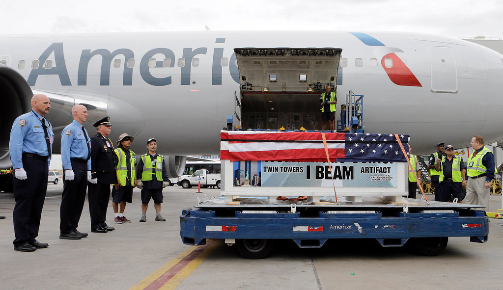. In this Thursday, Aug. 13, 2015 file photo, U.S. Customs and Border Protection agents and members of Miami-Dade Fire Rescue Department honor the arrival of a 2,000-pound World Trade Center steel beam enclosed in a case draped with the U.S. flag at Miami International Airport in Miami. The beam is destined for the Kennedy Space Center Fire Rescue\'s 9/11 memorial. (AP Photo/Alan Diaz)